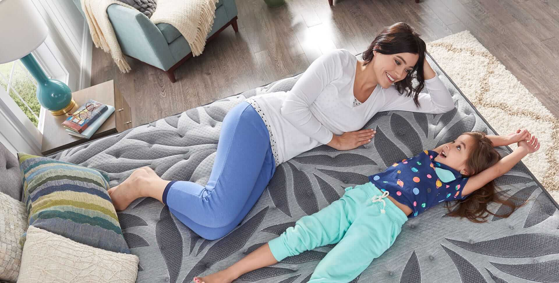 Mom and daughter lying on a Sealy® mattress